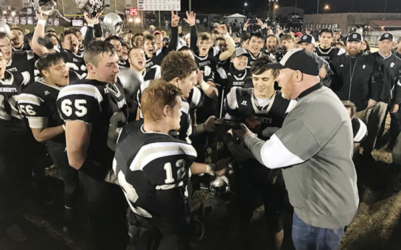 Robbinsville High School principal David Matheson (right) presents Black Knight players (from left) Carlos Wesley, Grady Garland, Kamron McGuire, Clayson Lane and Rylee Anderson with the 1A Western Regional Championship trophy, moments after a 28-14 win over Thomas Jefferson Classical Academy on Friday night. Photo by Kevin Hensley/editor@grahamstar.com