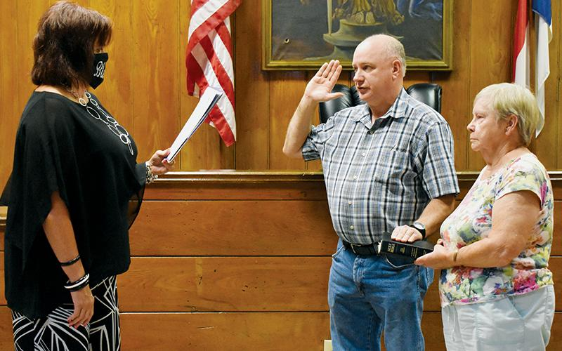 Graham County Clerk of Court Tammy Holloway (left) swears in Jerry Crisp as the new Graham County Sheriff on Tuesday afternoon. Holding the Bible is Jerry's aunt, Janet Crisp Lequire. Photo by Kevin Hensley/editor@grahamstar.com