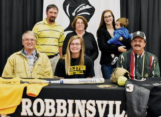 Lady Knights senior Gracye Burchfield (seated, center) signed with Pfeiffer University on Dec. 4. Seated with Burchfield are Larry Icenhower (left) and Gary Icenhower. Standing in back (from left) are Brent Icenhower, Barbara Icenhower, Hannah Lewis and Jordan Lewis. Photo by Kevin Hensley/editor@grahamstar.com