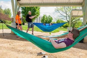 Students enjoy a sunny day at WCU's Electron Garden on the Green, a power-producing 10-kilowatt solar photovoltaic system and hammock hanging lounge.