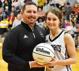 Following Monday's win, the Robbinsville Lady Knights recognized senior Cambrie Lovin for scoring her 1,000th career point during the KSA Christmas Tournament in Orlando on Saturday, Dec. 28. With Lovin is Lady Knights head coach Lucas Ford. Photo by Kevin Hensley/editor@grahamstar.com