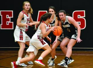 Robbinsville seniors Cambrie Lovin (left) and Karlyn Matheson eye an East Surry player during Thursday's game in Pilot Mountain. Photo by Kevin Hensley/editor@grahamstar.com