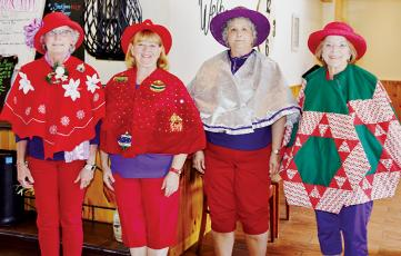 "Susan Lyons, Deborah Cheney, Joyce Mitchell and Glenda Raulerson (from left) participated in the ""Tree Skirts"" contest, one of several fun-filled festivities the Red Hat Ladies enjoyed at Saturday's ""Christmas in July."" Photo by Art Miller/amiller@grahamstar.com"