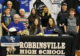 Robbinsville senior Gabby Hooper (center, seated) signed her letter of intent to play college softball with Brevard on Monday. Sitting with Hooper are parents Gabe and Crystal Hooper. Standing in back (from left) are brother Loxston Hooper, grandparents Clayton and Lana Hooper, sister Delaney Hooper, grandparents Patricia and Donald Cable, and brother Lleyton Hooper. Photo by Kevin Hensley/editor@grahamstar.com